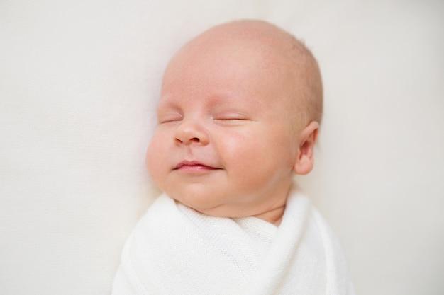 Neugeborenes baby auf einem weißen hintergrund. baby lächelt. junge schläft. weiße babywickel