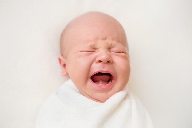 Neugeborenes baby auf einem weißen hintergrund. baby weint