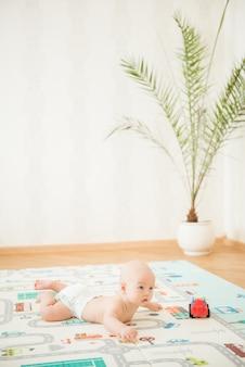 Neugeborenes baby, das auf seinem bauch auf der spielenden matte mit stadtautos liegt