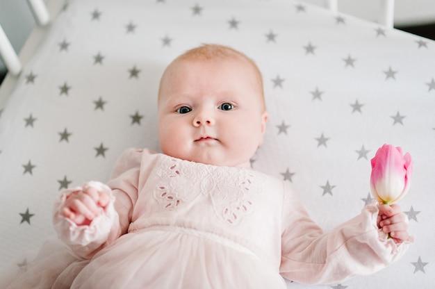 Neugeborenes baby, das blumenrosa tulpe hält und auf einem bett liegt. muttertag. flach liegen. draufsicht.
