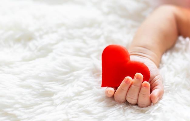 Neugeborenes baby, das ein herz in seinen händen hält