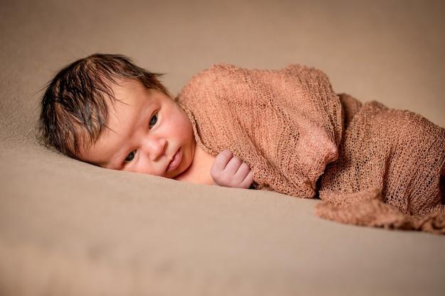 Neugeborenes baby, das friedlich mit kariertem stoff auf braunem hintergrund schläft.