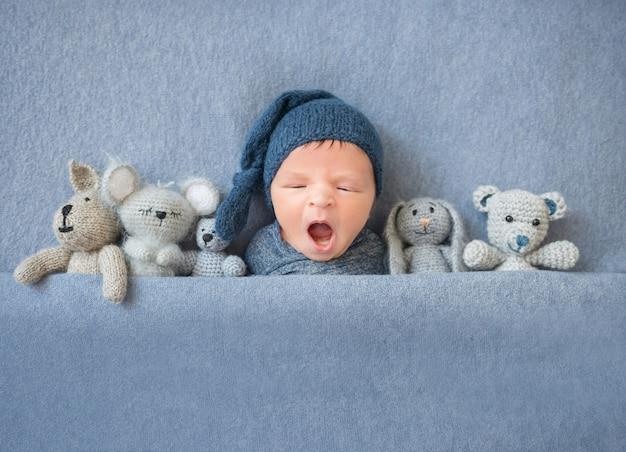 Neugeborenes baby, das gähnt und zwischen plüschtieren liegt