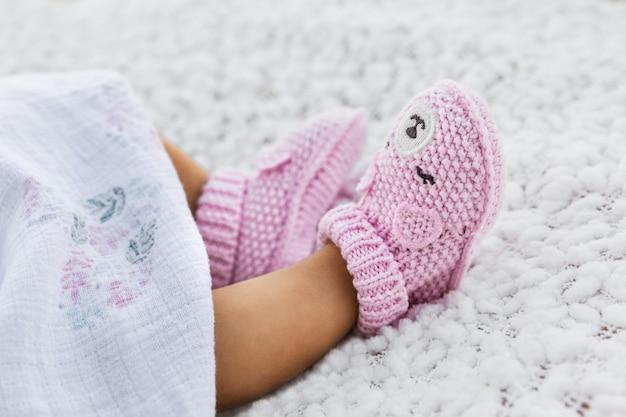 Neugeborenes baby, das gestrickte häkelarbeit gegen eine weiße decke trägt, rosa kinderschuhe