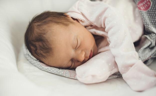 Neugeborenes baby, das gut schläft, während es warme kleidung trägt und auf einer babycouch liegt