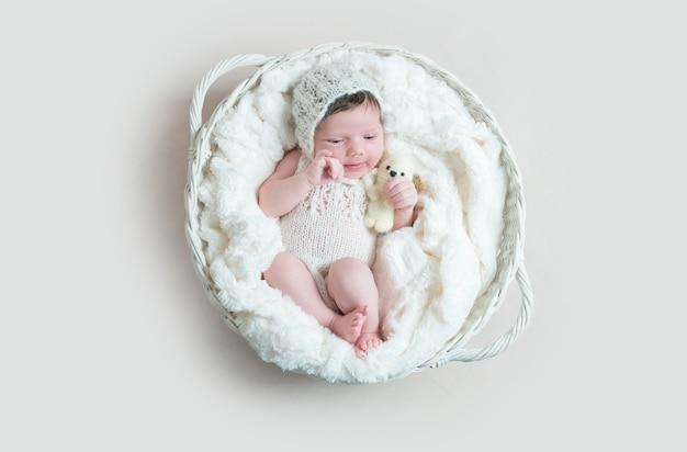 Neugeborenes baby, das im weidenkorb schläft