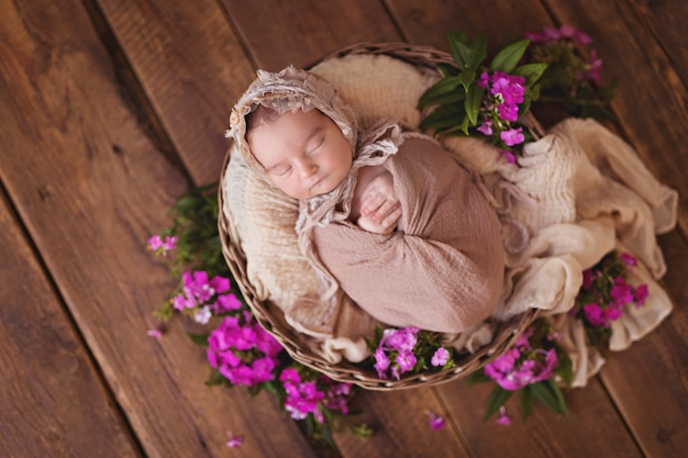 Neugeborenes baby, das in einem korb mit rosa gartenblumen schläft. das baby liegt auf dem rücken.