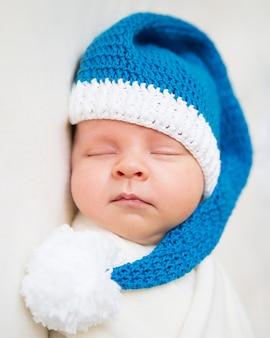 Neugeborenes baby, das in einer weihnachtsschutzkappe mit einem großen weißen bommel schläft