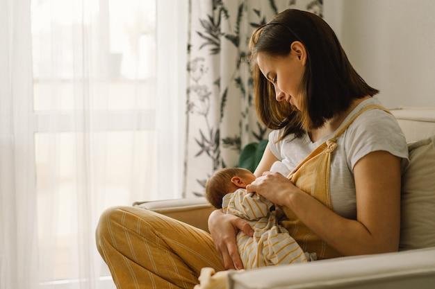 Neugeborenes baby, das milch von der brust der mutter saugt
