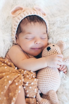 Neugeborenes baby, das mit einem spielzeug nahe bei dem gestrickten teddybären schläft