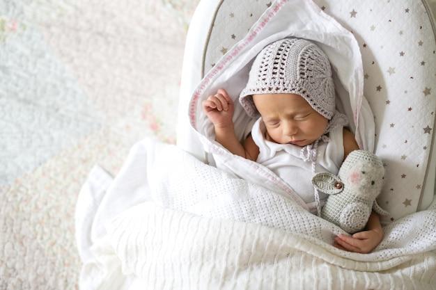 Neugeborenes baby, das mit spielzeug auf windel auf kokon schläft