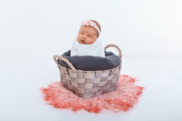 Neugeborenes baby eingewickelt in eine decke, die in einem korb schläft. konzept der kindheit, gesundheitswesen, ivf.