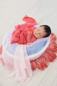 Neugeborenes baby eingewickelt in einer decke, die in einem korb schläft. konzept der kindheit, gesundheitswesen, ivf