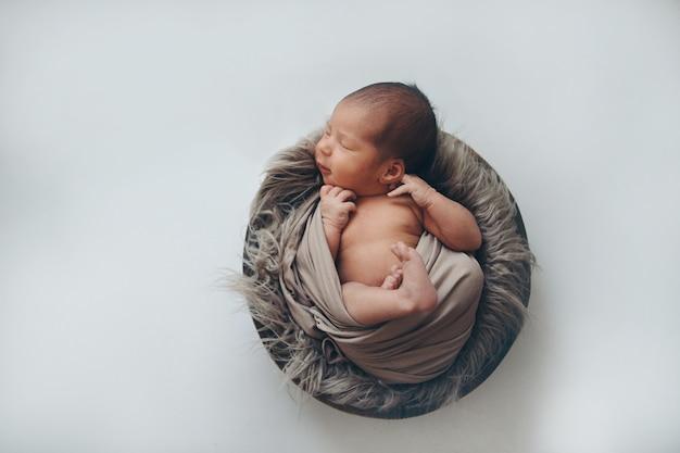 Neugeborenes baby eingewickelt in einer decke, die in einem korb schläft. konzept der kindheit, gesundheitswesen, ivf.