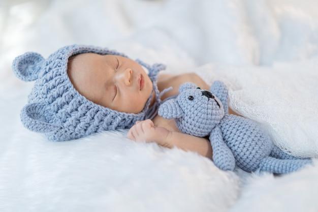 Neugeborenes baby im bärenhut schlafend auf pelzbett