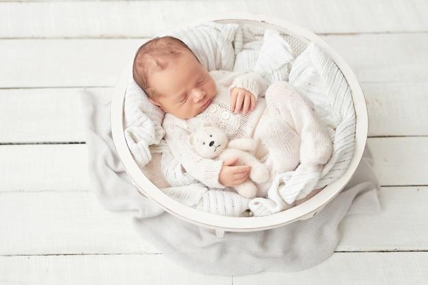 Neugeborenes baby in einem weißen anzug in der krippe