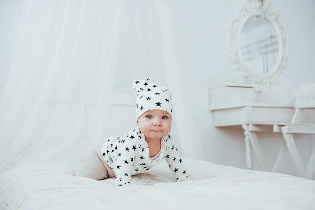Neugeborenes baby in einem weißen anzug und schwarzen sternen ist ein weißes weiches bett im studio
