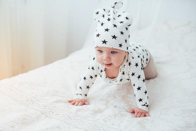 Neugeborenes baby in einem weißen anzug und schwarzen sternen ist ein weißes weiches bett
