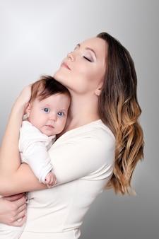 Neugeborenes baby in einer zarten umarmung der mutter am fenster