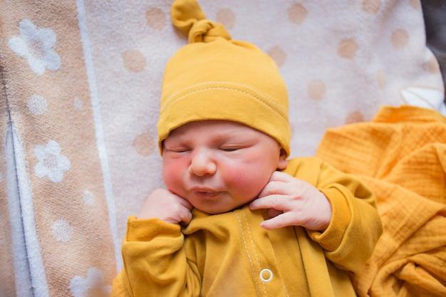 Neugeborenes baby in orangefarbenen kleidern. ein im herbst geborenes kind. neugeborene im krankenhaus