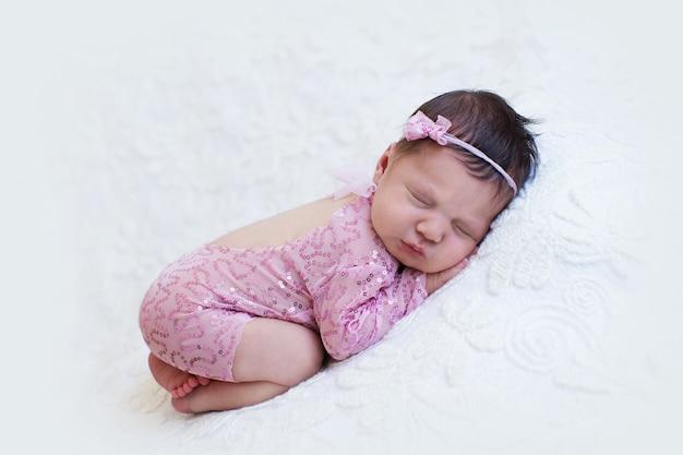 Neugeborenes baby in rosa, das auf ihrem bauch schläft
