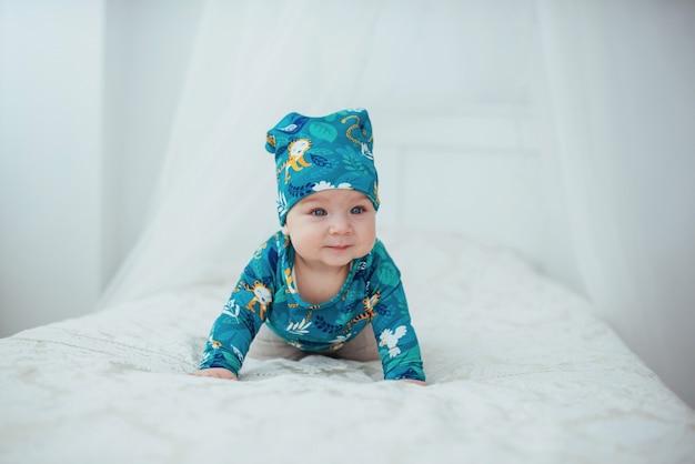 Neugeborenes baby kleidete in einer grünen klage an, die auf einem weichen bett liegt
