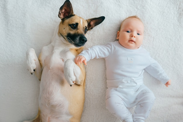 Neugeborenes baby liegend mit lustigem welpen auf bett.