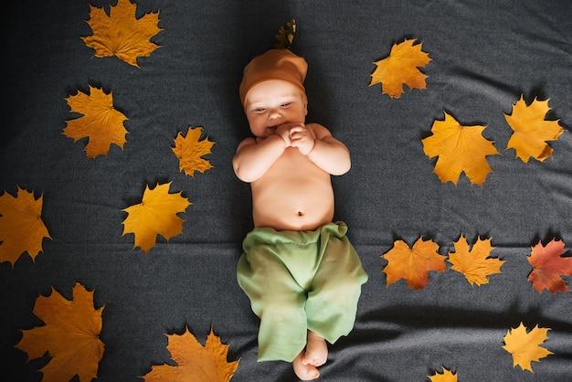 Neugeborenes baby liegt im herbst mit ahornblättern