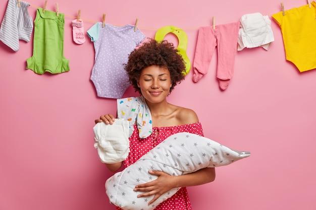 Neugeborenes baby liegt in den händen der mutter. erfreute lockige haarige frau fürsorgliche mutter hält schlafendes baby in decke auf händen gewickelt hat windel body auf schulter posen drinnen. glückliches familienkonzept.