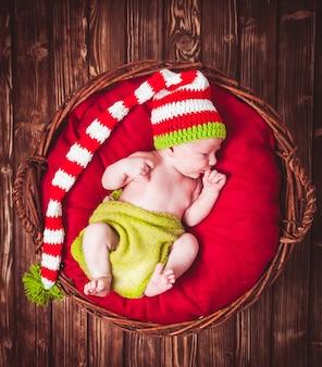 Neugeborenes baby mit hut, auf roter decke im korb