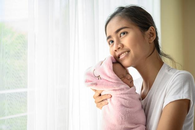 Neugeborenes baby schläft in der umarmung der mutter