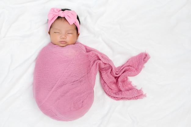 Neugeborenes baby schlafen in rosa stoffwickeldecke auf einem bett