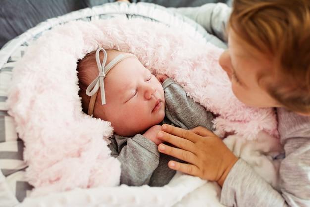 Neugeborenes baby schlafend und ihr älterer kleinkindbruder beobachten und berühren ihre hand