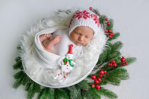 Neugeborenes baby schlafend unter weihnachtsbaum mit süßigkeiten in der hand, gesunder babyschlaf