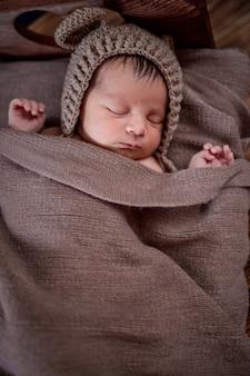 Neugeborenes baby, schönes kind liegt in brauner pelzdecke auf holzhintergrund, 10 tage altes mädchen, das im bett schläft. platz kopieren.