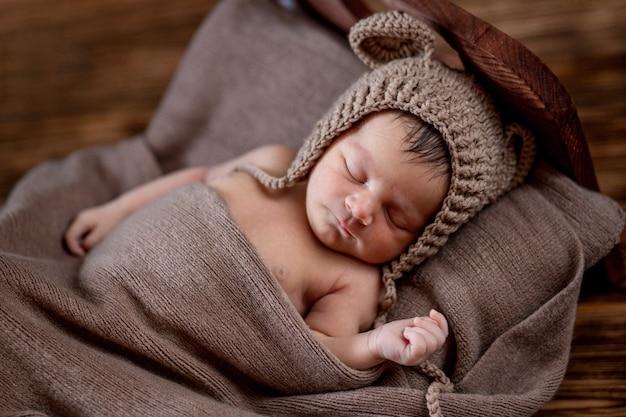 Neugeborenes baby, schönes kind liegt in brauner pelzdecke auf holzhintergrund, 10 tage altes mädchen, das im bett schläft. speicherplatz kopieren.