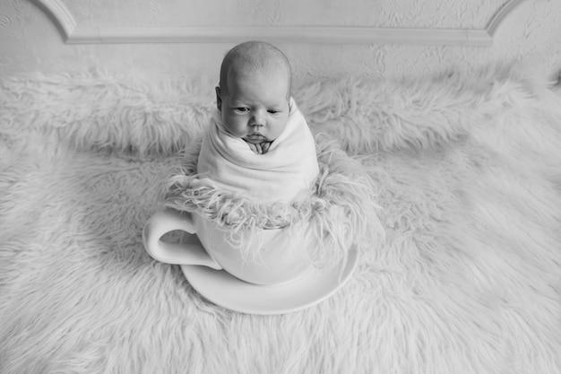Neugeborenes in einer großen tasse tee. kindheit, gesundheit, ivf, heiße getränke, frühstück