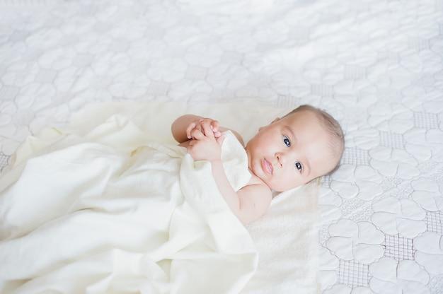 Neugeborenes kind, das im bett nach bad oder dusche entspannt.
