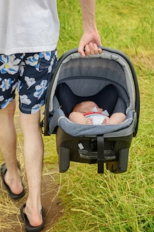 Neugeborenes kind in einem autositz in den händen eines jungen mannes.