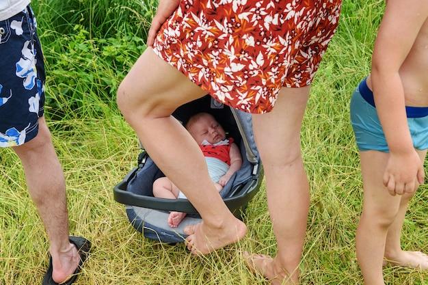 Neugeborenes kind in einem autositz in der natur zwischen den beinen seiner eltern und seines bruders.