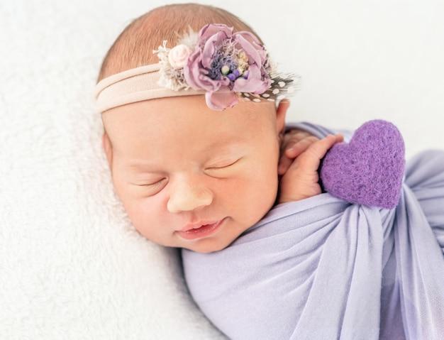 Neugeborenes kind in geblümten band und decke, mit einem zopf gesichert