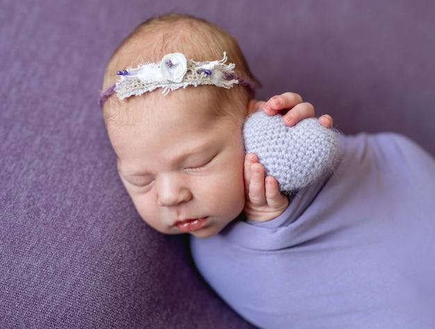 Neugeborenes kind mit gestricktem herzen