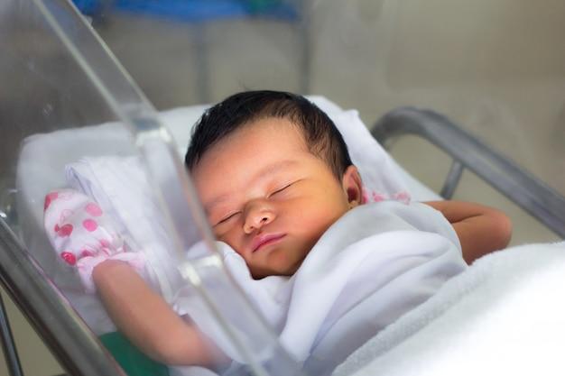 Neugeborenes kind schlafend in der decke im kreißsaal