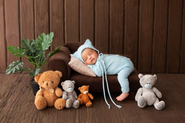Neugeborenes kleines sympathisches und hübsches baby schlafend auf kleinem braunem sofa im blauen pijamas, umgeben von pflanzen- und spielzeugbären