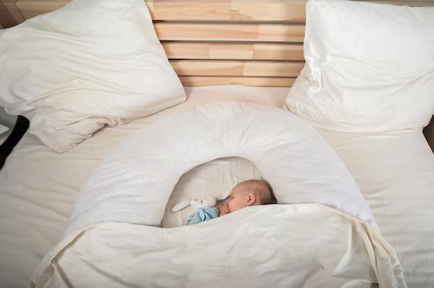 Neugeborenes kleinkind mit einem spielzeug auf dem bett nahaufnahme und kopierraum. das kind schläft auf einem großen bett