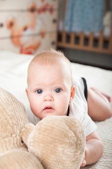 Neugeborenes kleinkind mit einem spielzeugbären auf dem bett nahaufnahme und kopierraum. lustiges baby und plüschtierbär