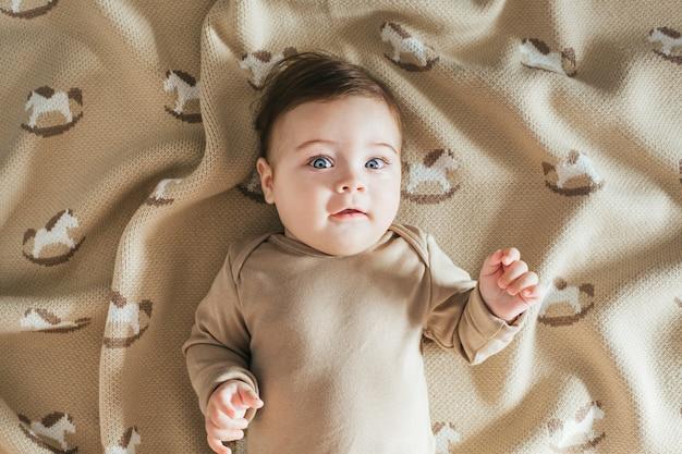 Neugeborenes kleinkindjungenporträt im beige bodysuit, das die kamera auf der karierten draufsicht betrachtet
