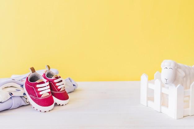 Neugeborenes konzept mit babykleidung und lächelndem schaf