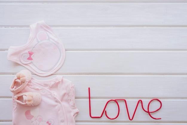 Neugeborenes konzept mit babykleidung und liebesbriefen