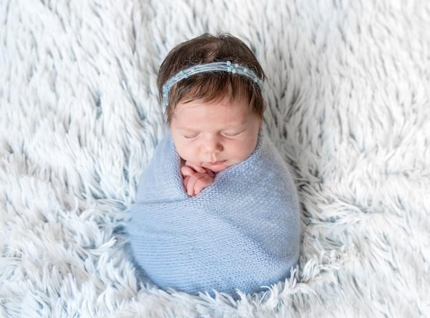 Neugeborenes mädchen im blauen wickel